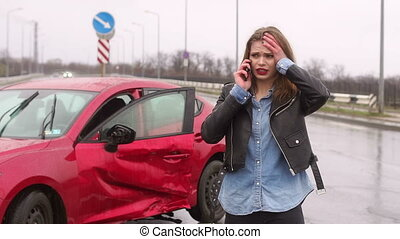 Portrait of a frightened girl near a broken car, she talking on the phone.
