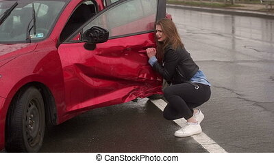 Portrait of a frightened girl near her broken car after a accident on a wet road