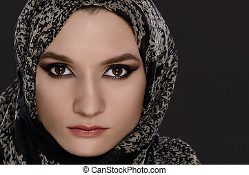 Portrait of a front view of a beautiful arab woman face with a head scarf