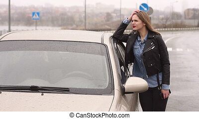 Portrait of a frustrated girl on an empty road in the rain near her broken car.