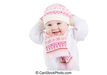 Portrait of a funny baby girl in a knitted hat, scarf and...