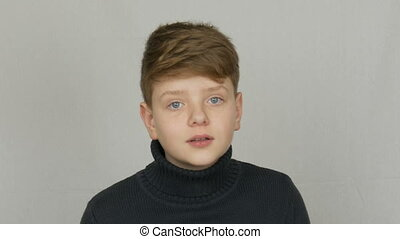 Portrait of a funny blond and blue-eyed teenager boy showing...