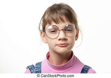 Portrait of a funny girl in glasses squinting eyes on a white background