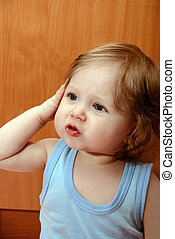 Portrait of a funny little boy in blue shirt.