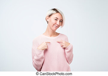 Portrait of a funny smiling woman pointing fingers on herself