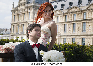 Portrait of a girl and a guy sitting on a bench. Wedding in Paris