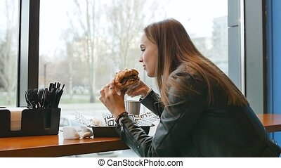 Portrait of a girl close-up with a hamburger in his hand. A young pretty woman eating a hamburger at a cafe. Food, Fast Food, Nutrition