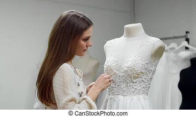 Portrait of a girl creating a wedding dress by exclusive order sewing fabrics and rhinestones on a dress dressed in a mannequin. production of wedding dresses. Little business