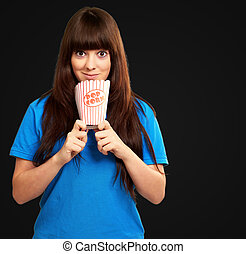 portrait of a girl holding empty popcorn packet on black...