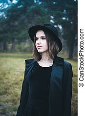 Portrait of a girl in a black hat in the gloomy forest