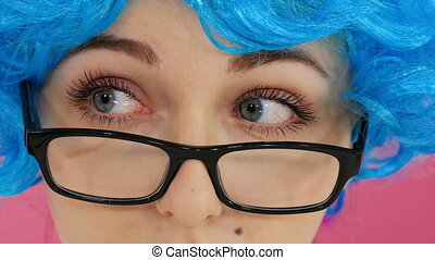 Portrait of a girl in a blue wig and glasses on a crimson...