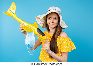 Portrait of a girl in a hat holding a yellow toy airplane and a medical mask while posing for the camera. Travel concept during a pandemic on a blue background.