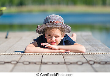 portrait of a girl in a hat on a wooden pier near the lake