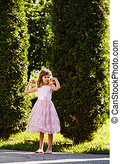 Portrait of a girl in a lush pink dress in the park.