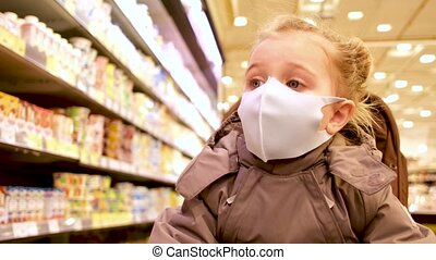 Cute little girl wearing protective surgical face mask sitting in stroller, in super market store shopping being safe protection from corona virus COVID-19 and other airborne bacterial diseases