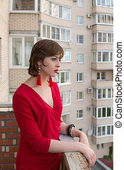 girl in a red dress on the balcony
