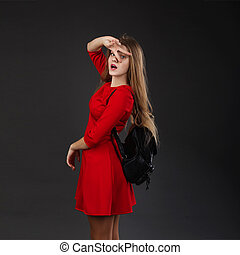 Portrait of a girl in a red dress with a black leather backpack on her shoulder.