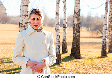 portrait of a girl in a white coat on the background of birch tr