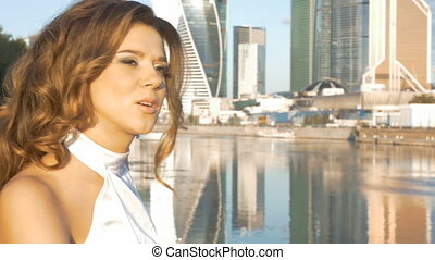 Portrait of a girl in a white suit on the city embankment. Early in the morning.