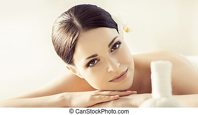 Portrait of a girl in spa. Massaging therapy procedure. Skin care and massage concept.