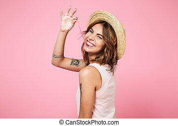 Portrait of a girl in summer hat looking at camera -...