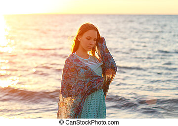 portrait of a girl in the sea at sunset in rays of sun, vacation and relaxation