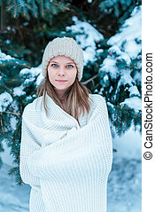 Portrait of a girl in the winter forest on background of snow-covered trees. In a white plaid and white hat. Happy smiles.