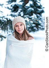 Portrait of a girl in the winter forest on background of snow-covered trees. In a white plaid and white hat. Beautiful woman in the park in winter.