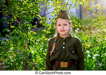Portrait of a girl in uniform on a green background. Victory Day