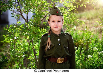 Portrait of a girl in uniform on a green background. Victory Day .