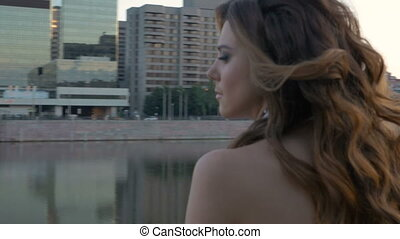 Portrait of a girl in white clothes. Early morning, there are no people on the city waterfront
