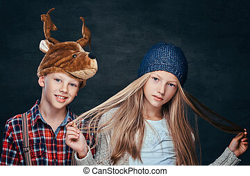 Portrait of a girl in winter hat and smiling boy in deer hat, looking at the camera
