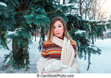 Portrait of a girl in winter, striped sweater, background green branches spruce, happy warms herself white warm mittens. Emotions comfort of weekend getaway winter resort. In white scarf.
