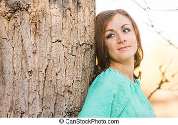 Portrait of a girl leaning against a tree