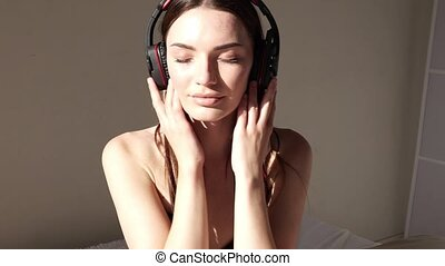 Portrait of a girl listens to music in large headphones