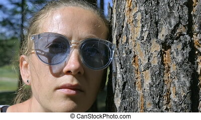 Portrait of a girl looking at the camera leaning against a tree trunk
