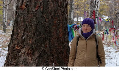 Portrait of a girl near a big old tree, larch