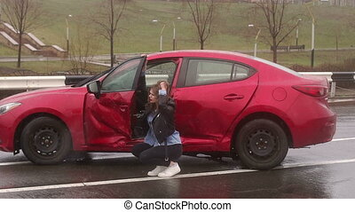 Portrait of a girl near her wrecked car after a severe accident on a wet road.