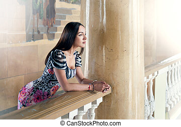 Portrait of a girl on a balcony with columns