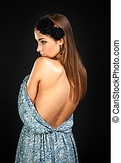 portrait of a girl on a black background with a bare back.