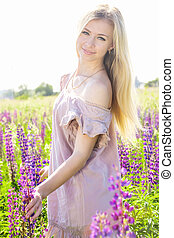 Portrait of a girl on the field with lupines