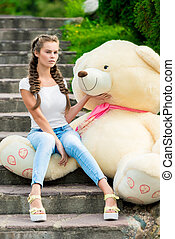 portrait of a girl on the stairs in a park with a huge teddy bear posing
