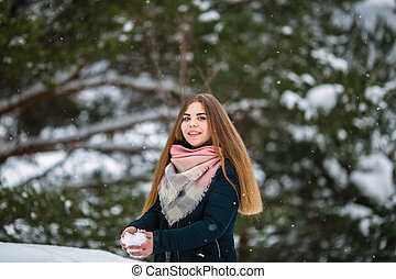 Portrait of a girl playing with snow in an amazing winter.