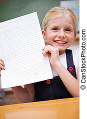Portrait of a girl showing her school report