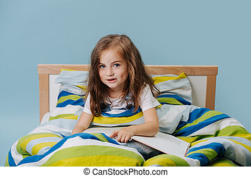 portrait of a girl sitting in bed with a book.