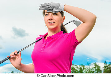 portrait of a girl with a golf club looking out for the flight path of the ball