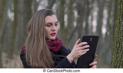 Portrait of a girl with a tablet in the forest. Slowly