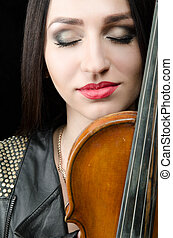 Portrait of a girl with a violin, with closed eyes