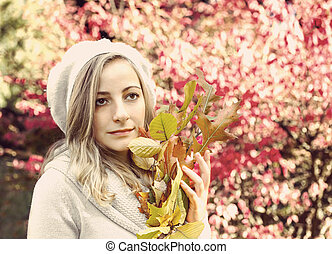 Portrait of a girl with autumn leaves with retro filter effect
