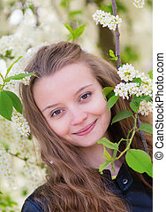 Portrait of a girl with blooming bird-cherry tree